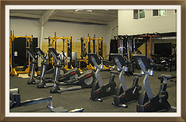 Lineup of Stationary Bikes and Other Equipment in High School Gym