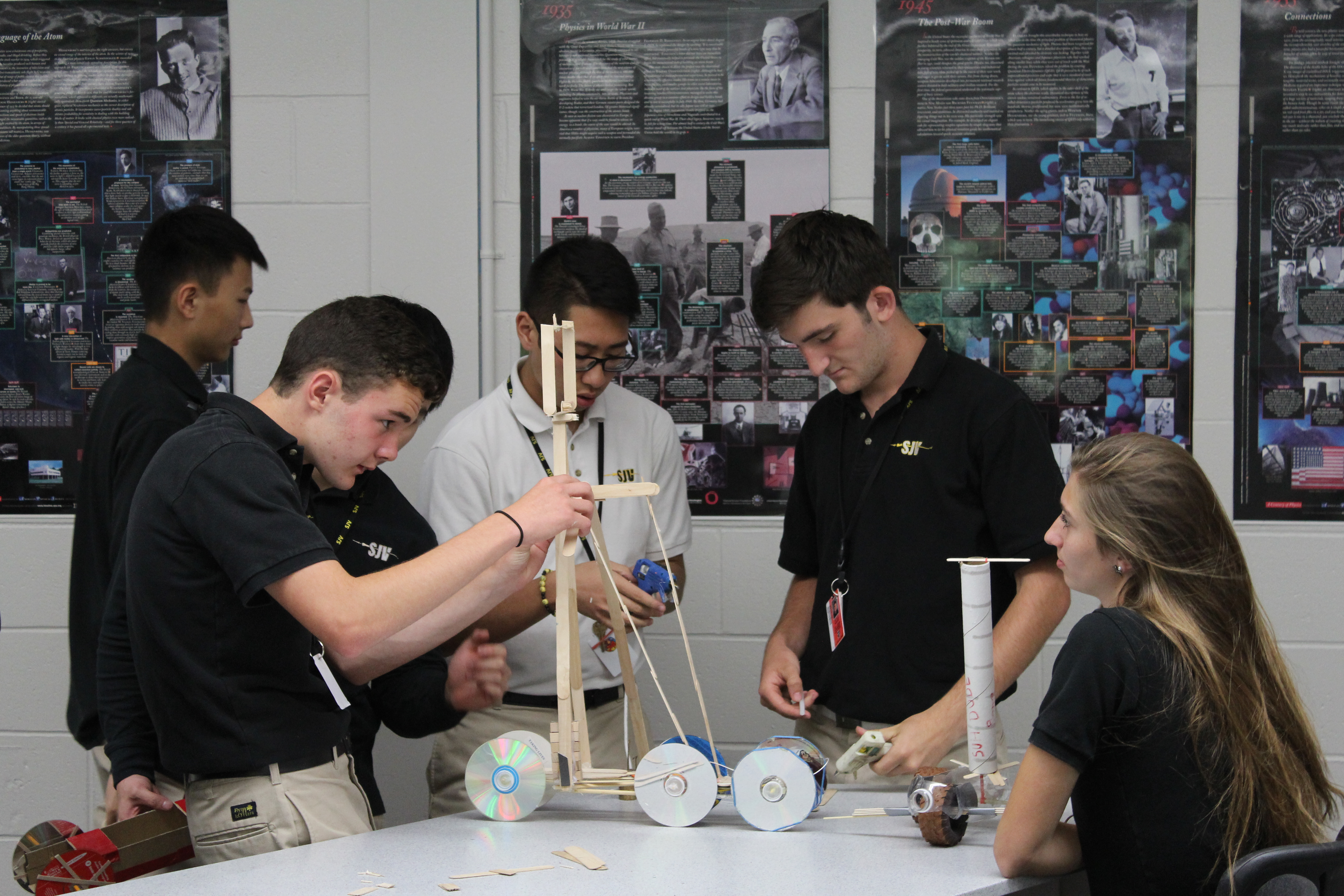 Group of Students Performing Physics Experiment at Table